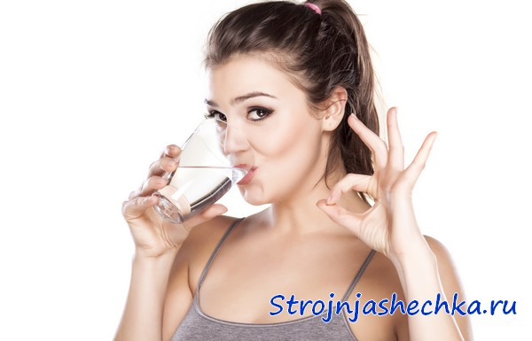 Девушка пьет из стакана воду